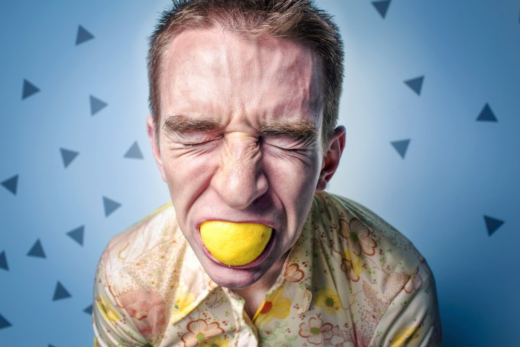 Man in stress with lemon in his mouth